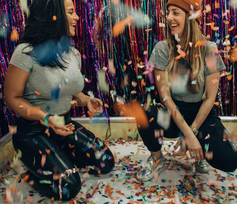 Two girls playing games in confetti